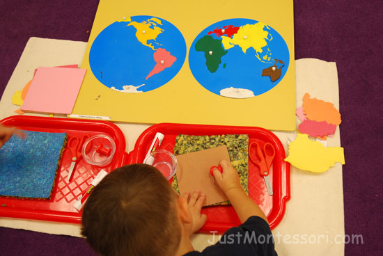 An older child is working on poking out the continents to make a hemisphere map.