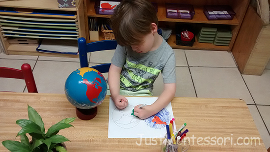 A younger child coloring a hemisphere map.